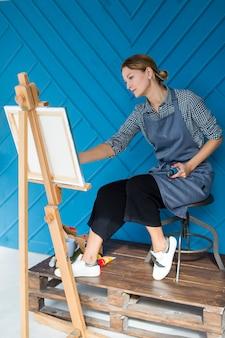 Сосредоточенный художник, рисующий на холсте