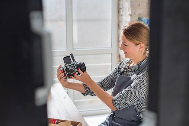 Женщина смотрит на винтажную камеру