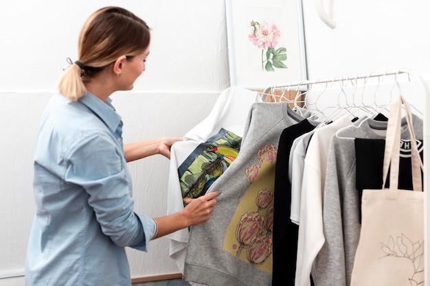 Женщина смотрит на одежду среднего выстрела