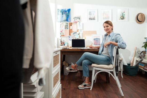 Счастливый художник сидит в творческом рабочем пространстве