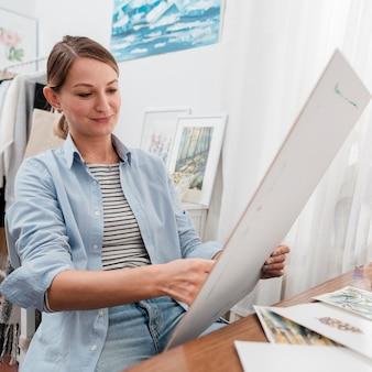 Счастливый художник держит произведение искусства среднего снимка
