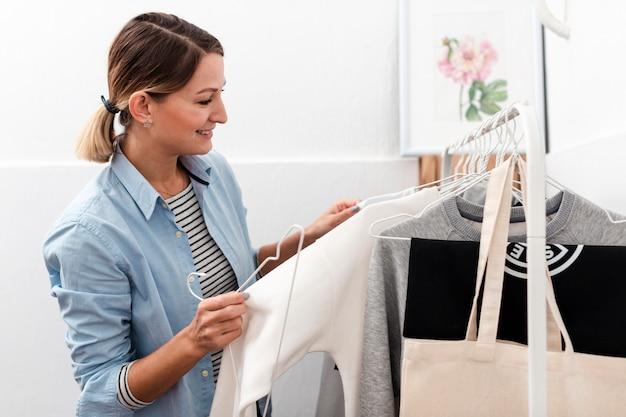 Счастливая женщина смотрит на одежду