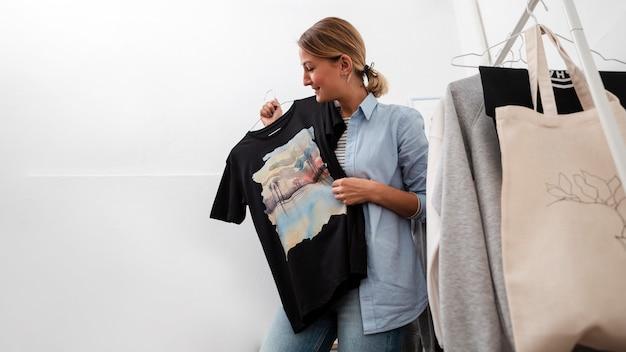 Женщина держит футболку и улыбается