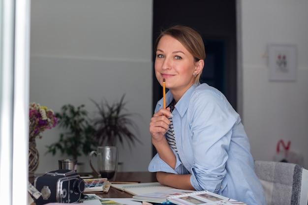 Женщина держит карандаш и позирует на стол