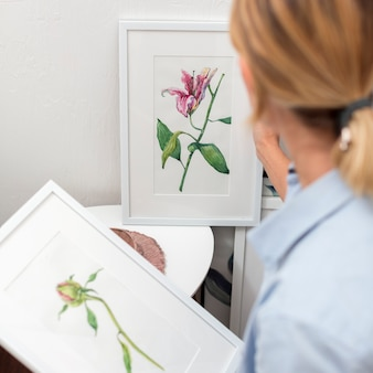 花の絵を保持している女性の背面図