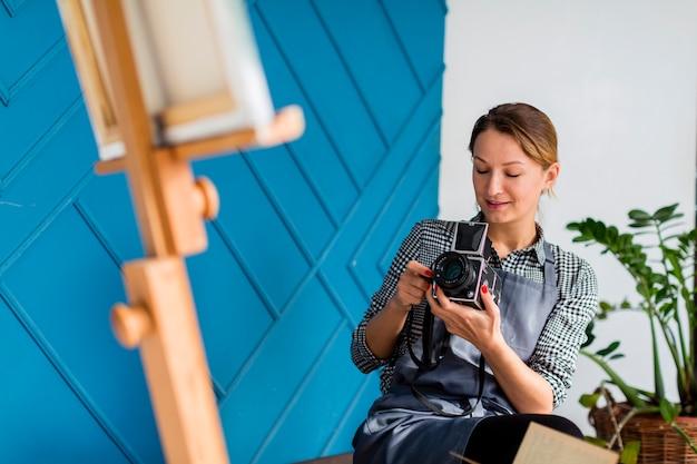 Женщина фотографирует холст на мольберте