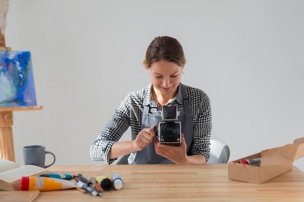 レトロなカメラを保持しているエプロンのアーティストの正面図