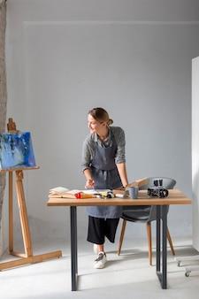 エプロンの机の上で作業するアーティスト