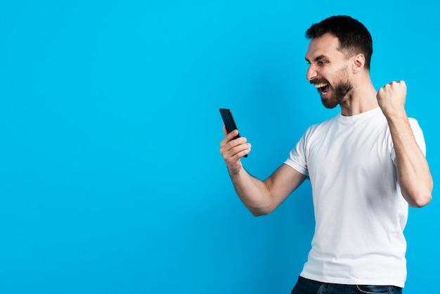 スマートフォンを押しながら勝利のポーズの男