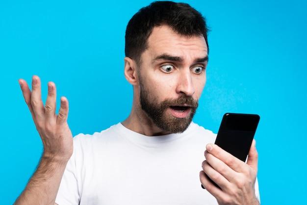 Шокированный мужчина смотрит на смартфон