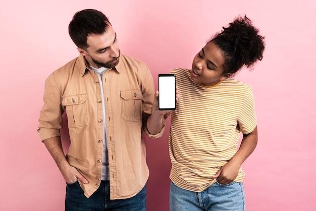 スマートフォンに興味をそそられるポーズのカップル