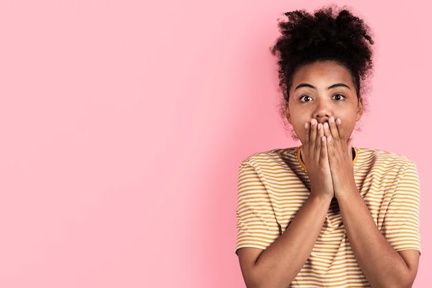 Удивленная женщина позирует с руки в рот