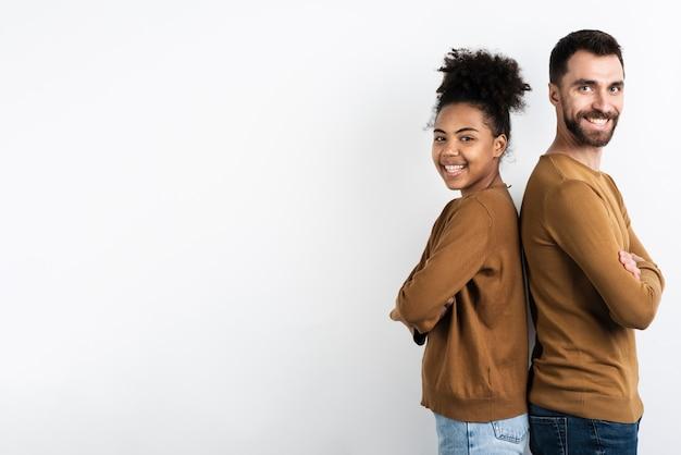 Счастливая пара позирует спина к спине