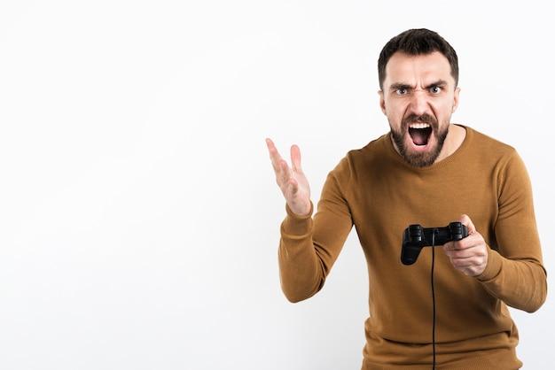 Злой человек держит игровой контроллер