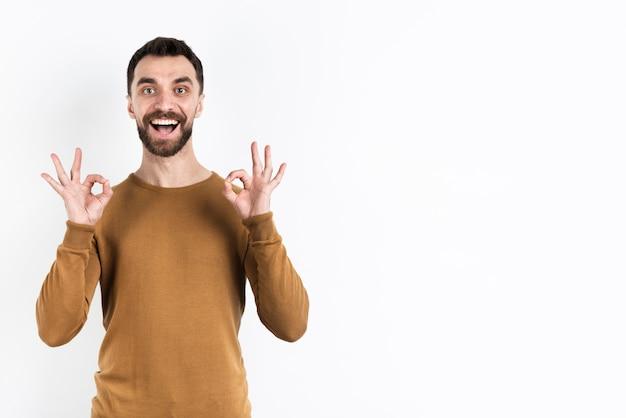 Человек делает хорошо знаком с обеими руками и улыбается