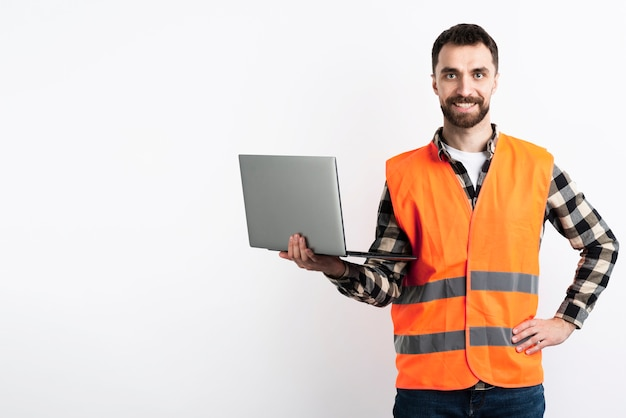 ノートパソコンと安全ベストでポーズの男