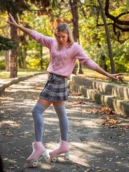 Женщина глупо позирует на улице с роликовыми коньками
