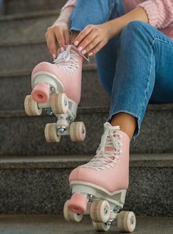 Женщина на лестнице надевает роликовые коньки
