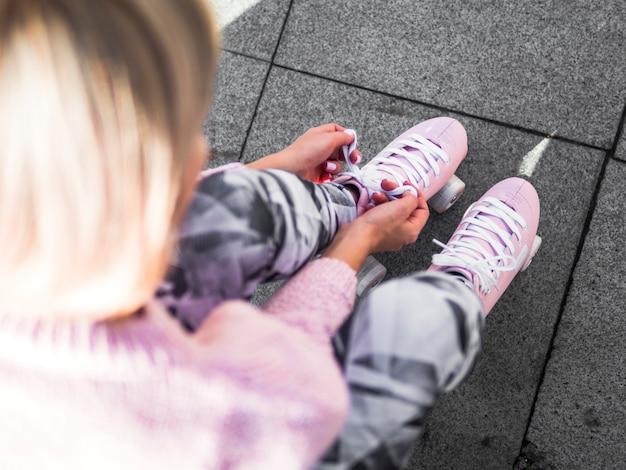ローラースケートで靴ひもを結ぶ女性の高角