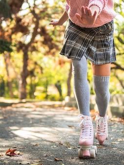 Вид спереди женщины в юбке и носках на роликовых коньках