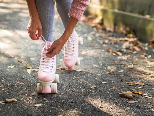 Конец-вверх женщины связывая шнурок на коньках ролика с космосом экземпляра