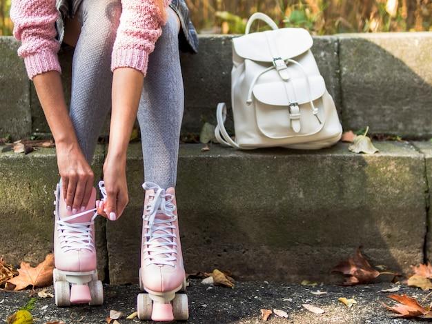 Вид спереди женщины в носках с рюкзаком и роликовыми коньками