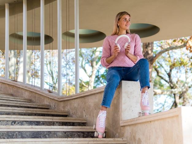 ヘッドフォンを保持しているローラースケートの女性のローアングル