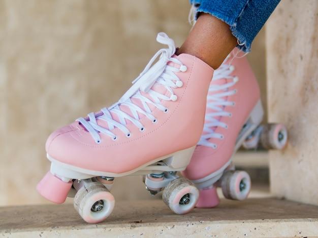 ジーンズを持つ女性にローラースケートのクローズアップ