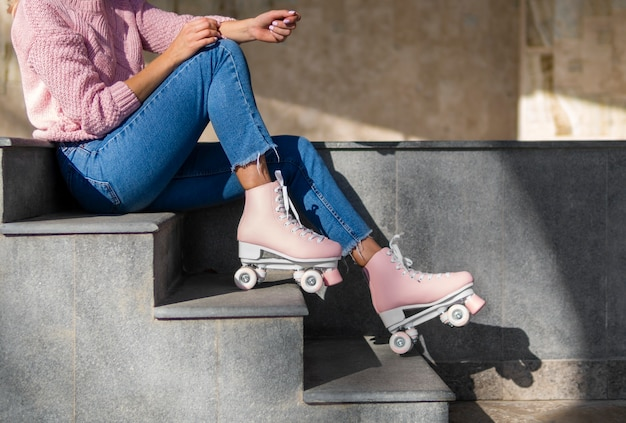 Вид сбоку женщины в джинсах на лестнице с роликовыми коньками