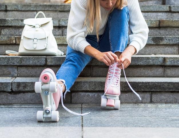 ローラースケートで靴ひもを結ぶ階段の女性