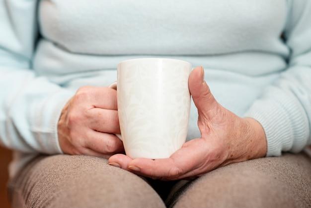 お茶のカップを持つクローズアップ女性