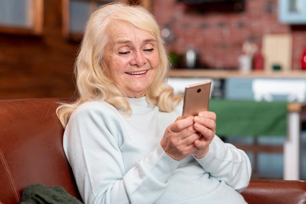 電話を見て年配の女性