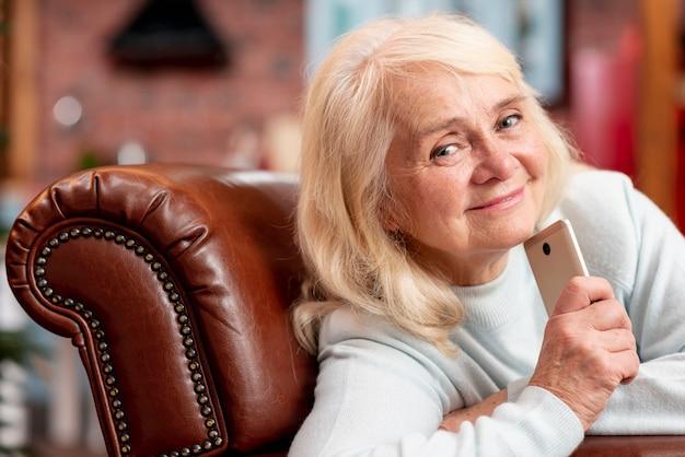 Пожилая женщина дома с мобильным телефоном
