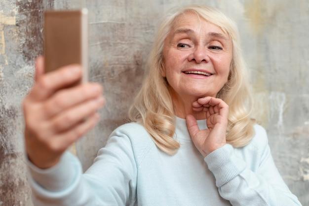 Пожилая женщина, принимая селфи с мобильного