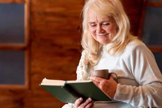 お茶を飲むと読んでいる年配の女性