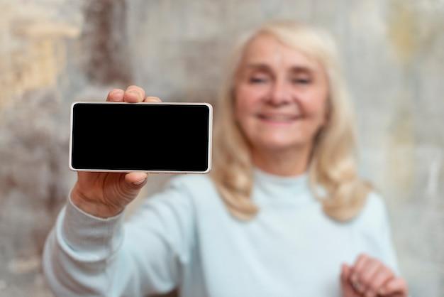 高角度の年配の女性が携帯電話をホールド