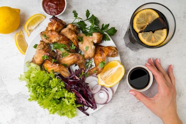 Вид сверху вкусные куриные крылышки с салатом