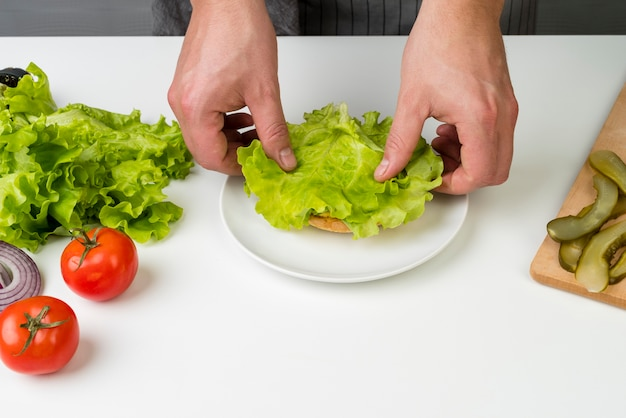 Руки готовят вкусный гамбургер