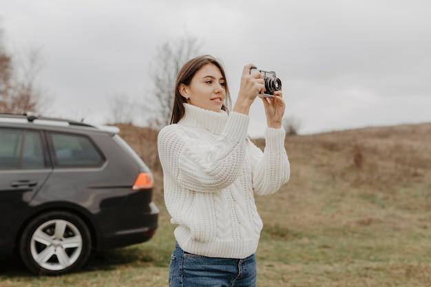 屋外で写真を撮る素敵な女性