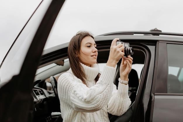 サイドビューの女性が写真を撮る