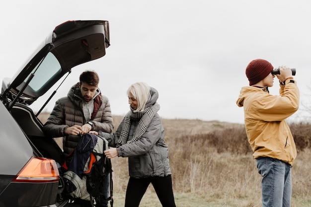 Друзья берут рюкзак из машины