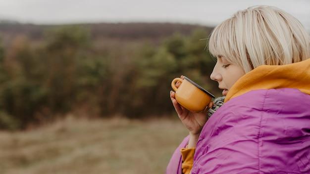 お茶を飲む自然の中で若い女性