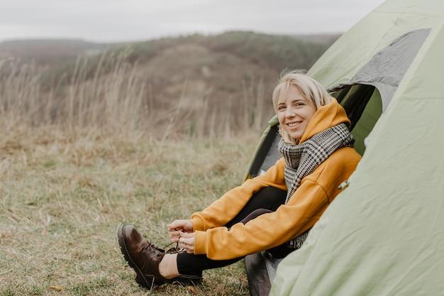 テントに座っている高角度の女性
