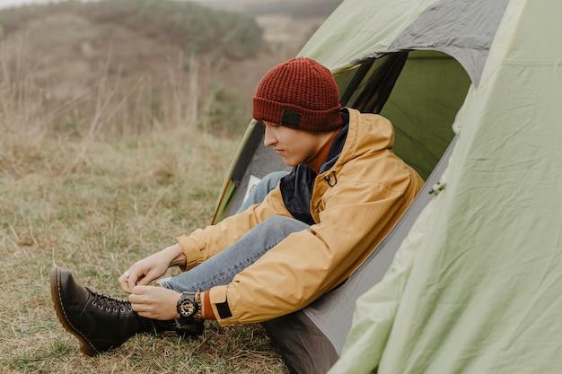 Боковой вид человек в палатке связывает шнурки