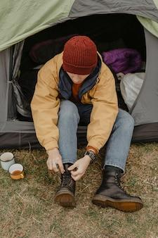 Высокий угол человек в палатке связывает шнурки