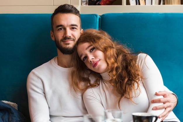 屋内でポーズ美しい若いカップル