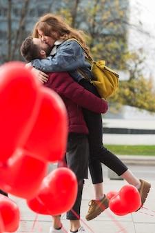 フルショットかわいいカップルのキス