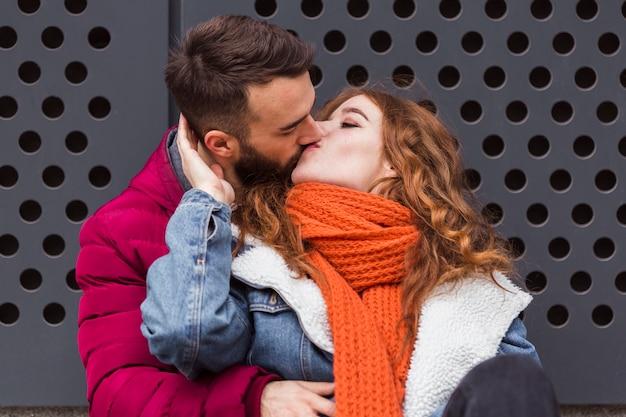 正面の素敵な若いカップルがキス