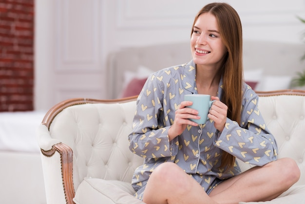 Женщина носит пижаму и пьет чай