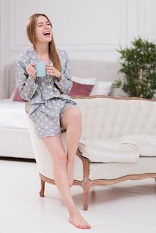 Молодая женщина с чашкой чая смеется